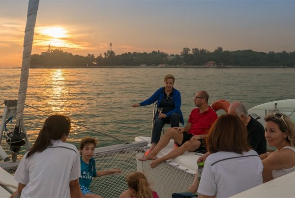 A group of people sitting on the deck of a yacht as the sun sets